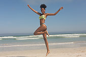 Young African American woman in green bikini jumping on the beach