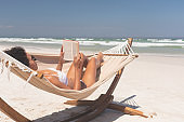 Woman relaxing on hammock at beach on a sunny day