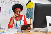 Female fashion designer using digital tablet at desk