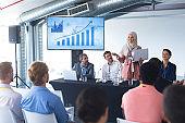 Female speaker with laptop speaks in business seminar