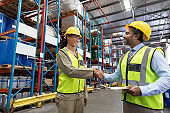 Male and female staff shaking hands with each other in warehouse