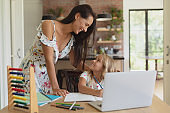 Mother helping her daughter with homework in a comfortable home
