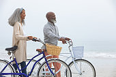 Couple smiling while holding bicycles at the beach