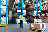 Male staff using pallet jack in warehouse