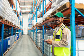 Male worker holding digital tablet and looking at camera in warehouse