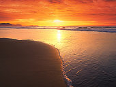 beautiful sunset on beach with a wave on the shore in summer
