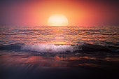 red sunset on beach with a wave on the shore and big sun
