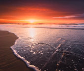 beautiful sunset on beach with a wave on the shore