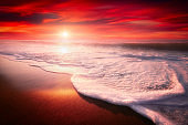 red sunset on beach with a wave on the shore