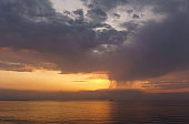beautiful sunset over the sea with rain showers