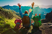 happy father and kids travel in sunset mountains