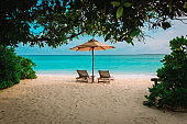 Two beach chairs on tropical vacation at sea