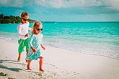 happy cute little girl and boy run at beach
