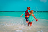 little girl and boy run play with water on beach