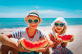 happy cute boy and girl eating watermelon at beach
