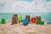 Sand castle on the beach with toys, family vacation