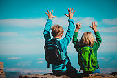 Happy boy and girl hiking in mountains, kids enjoy vacation