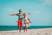 happy cute boy and girl run play at beach