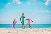 happy kids- boy and girls- dance at beach, family enjoy vacation at sea