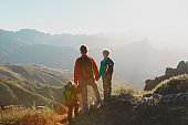 Father with kids travel in sunset mountains
