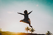 happy little girl jumping at sunset beach