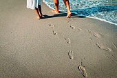 mother and daughter walking on beach leaving footprint in sand