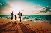 happy family with kids on play on sunset beach