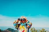 family travel- little girl with binoculars exploring nature