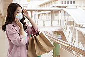 Asian business woman wearing a protective face mask on a city street with air pollution. Facial hygienic mask for Safety outdoor environmental awareness concept