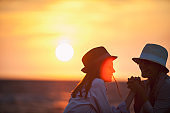 Silhouettes of two women together on the seaside at sunset