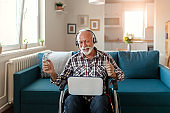 Disabled Senior Man in a Wheelchair with Laptop and Headphones
