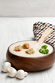 Creamy mushroom soup on white wooden table