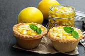 Egg custard tarts with jellied lemon on black stone background