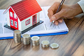 A woman signs a purchase agreement for a house in a real estate agent.  Contract Buy - sell house concept.