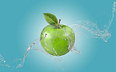 Green Apple Up In The Air While Water Splashes Against Blue Background
