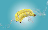 Bananas Up In The Air While Water Splashes Against Blue Background