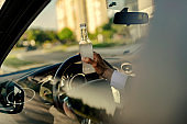 Driver Holds a Bottle of Alcohol