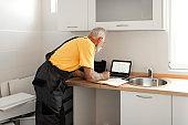 Senior Handyman using Laptop while Fixing Kitchen Cabinet