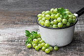 Fresh ripe green gooseberry on wooden background