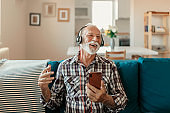 Portrait of Senior Man Listening Music Over Smartphone and Headphones