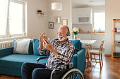 Disabled Senior Man in a Wheelchair Using Smartphone and Headphones