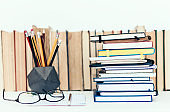 Notebooks piles, stack of books education back to school background, textbooks, glasses and pencils in holder with copy space for text