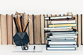 Pile of notebooks, many books and textbooks, glasses and pencils in concrete holder with copy space for text, education back to school background