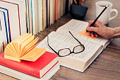 Stack of books education background, female hand makes notes in open notebook. Glasses, pens and pencils in holder, cup of tea with lemon