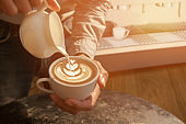 Barista making cappuccino with latte art.