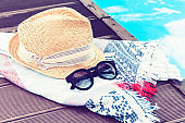 Vintage summer wicker straw beach hat, sun glasses and cover-up beachwear wrap near swimming pool, tropical background