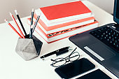 Stack of books, smartphone, laptop, glasses and pencils in holder, office business background for education learning concept