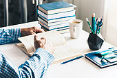 man reading book on modern stylish work place with office supplies, glasses, notebooks and books, desk work concept in white and blue colors
