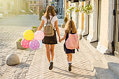 View from the back, two schoolgirls of primary and secondary schools holding hands walking along city street, with colored  balloon, in school uniform with backpacks. Back to school