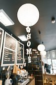 Modern coffee shop, interior, bar counter, focus on white round paper lamp and the word home in wooden letters. Home cafe concept